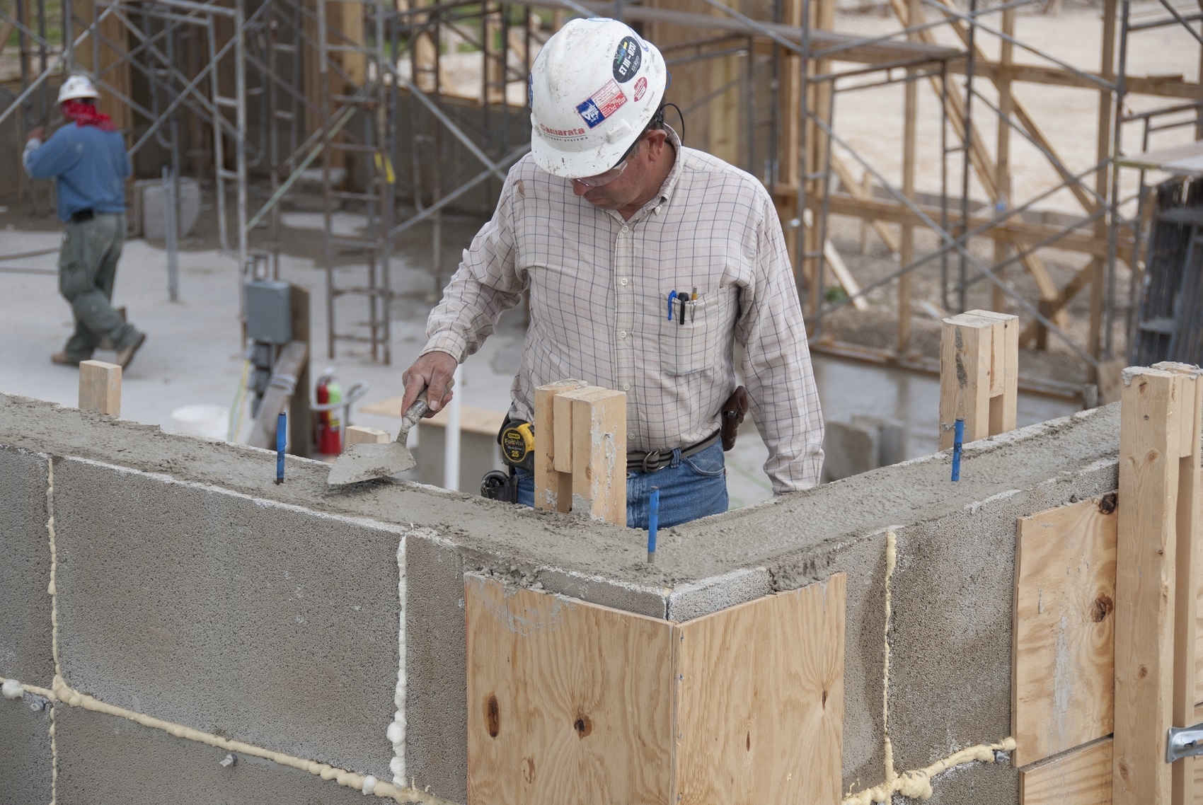 Construction worker wearing a white hard hat uses trowel to smooth mortar on the top of a concrete block wall.