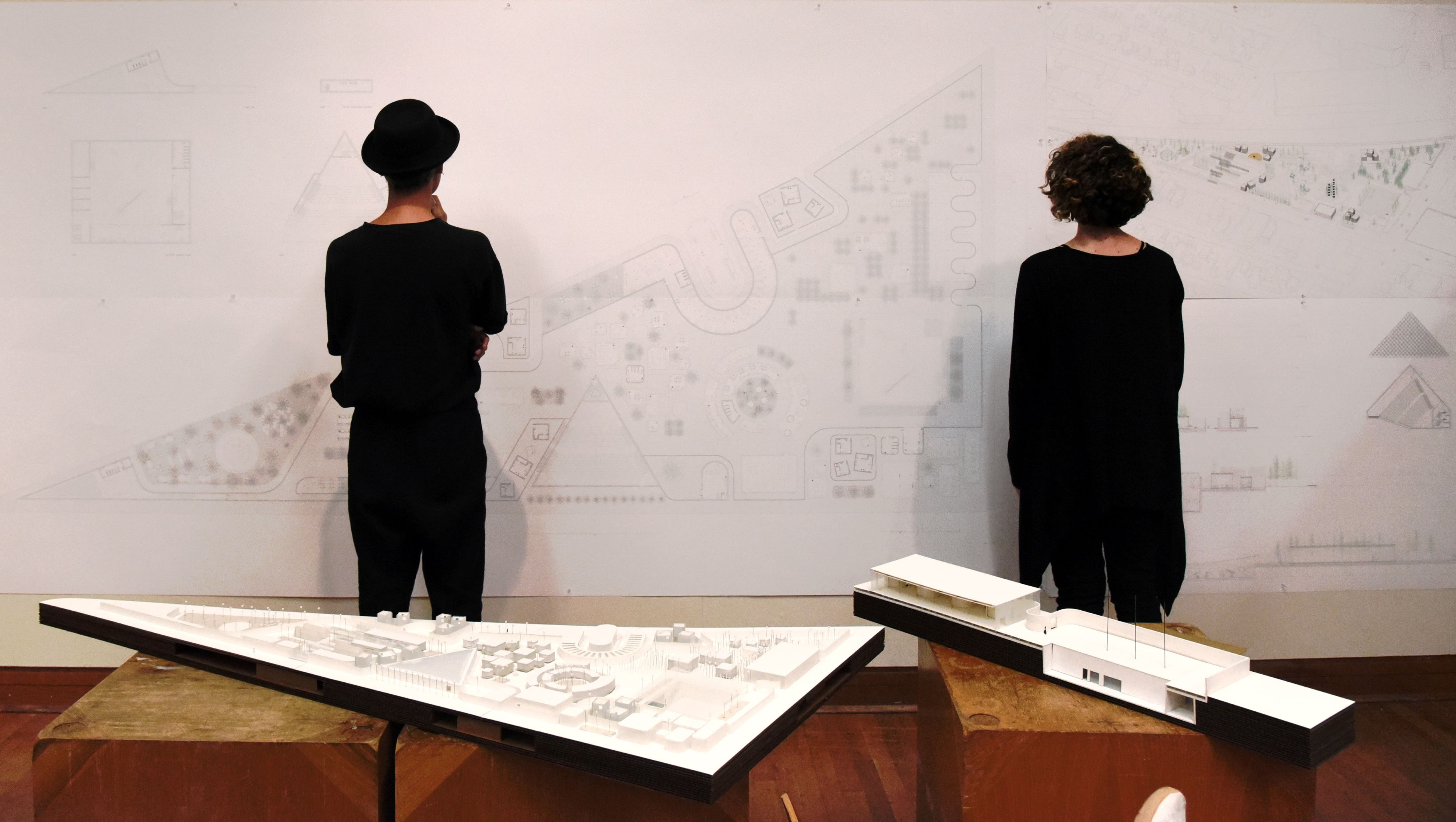 Two students in black looking at a wall of drawings during final review, foregrounded with a physical model