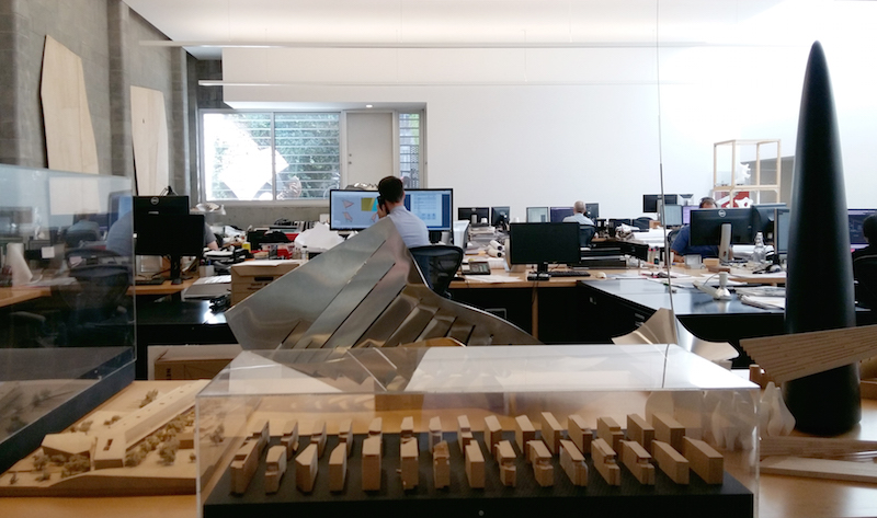 Artistic shot showing an architecture model in the foreground, someone working at an office computer in the background