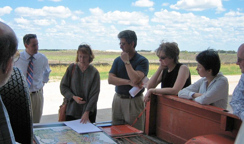 Group of people in discussion, standing in a circle around a map.