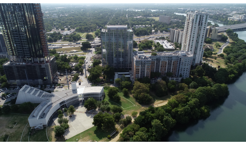 Drone shot of a section of downtown Austin with Lady Bird Lake and buildings in the forefront, Interstate-35 in the background