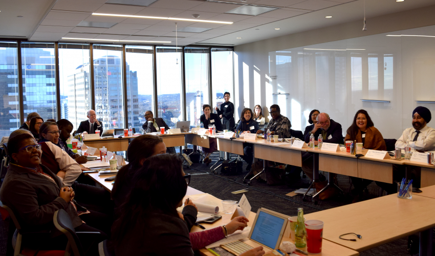 Mayors and CSD team meet at tables in board room overlooking downtown Austin