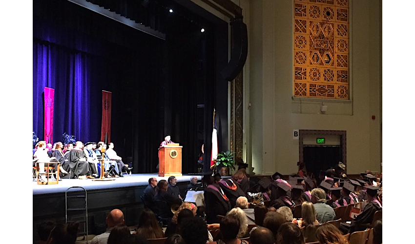 Dean Addington giving remarks at commencement, at podium in Hogg Memorial Auditorium