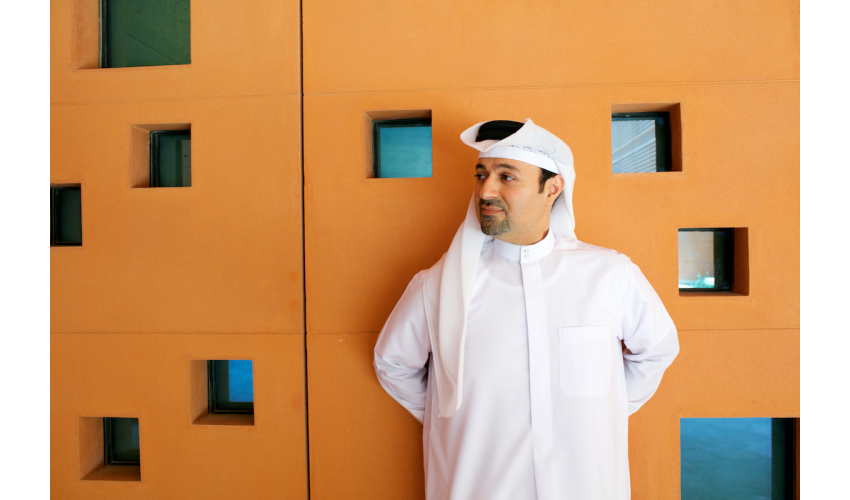 Dr. Khaled Alawadi standing next to orange wall
