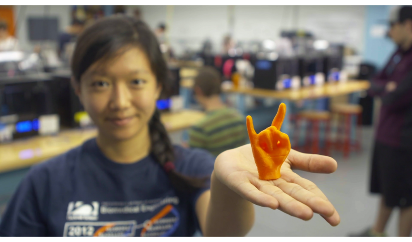 Student holding 3D printed hand doing the Longhorn symbol