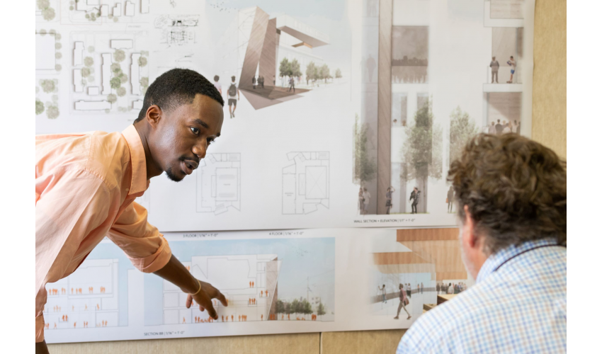 Student in an orange shirt looking at a professor while pointing to his drawing on the wall