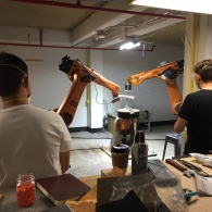Two students seen from behind watching the KUKA robotic arm in action