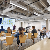 A new classroom in the West Mall Building with students seated at long desks. One student points to a large digital screen.