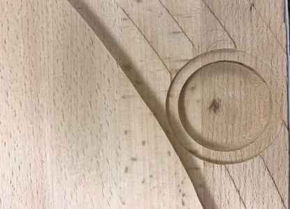 Closeup of a wood table top with shapes routed into it