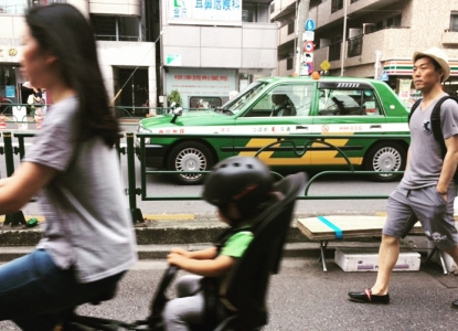 Woman riding bike with baby in Tokyo as man walks by