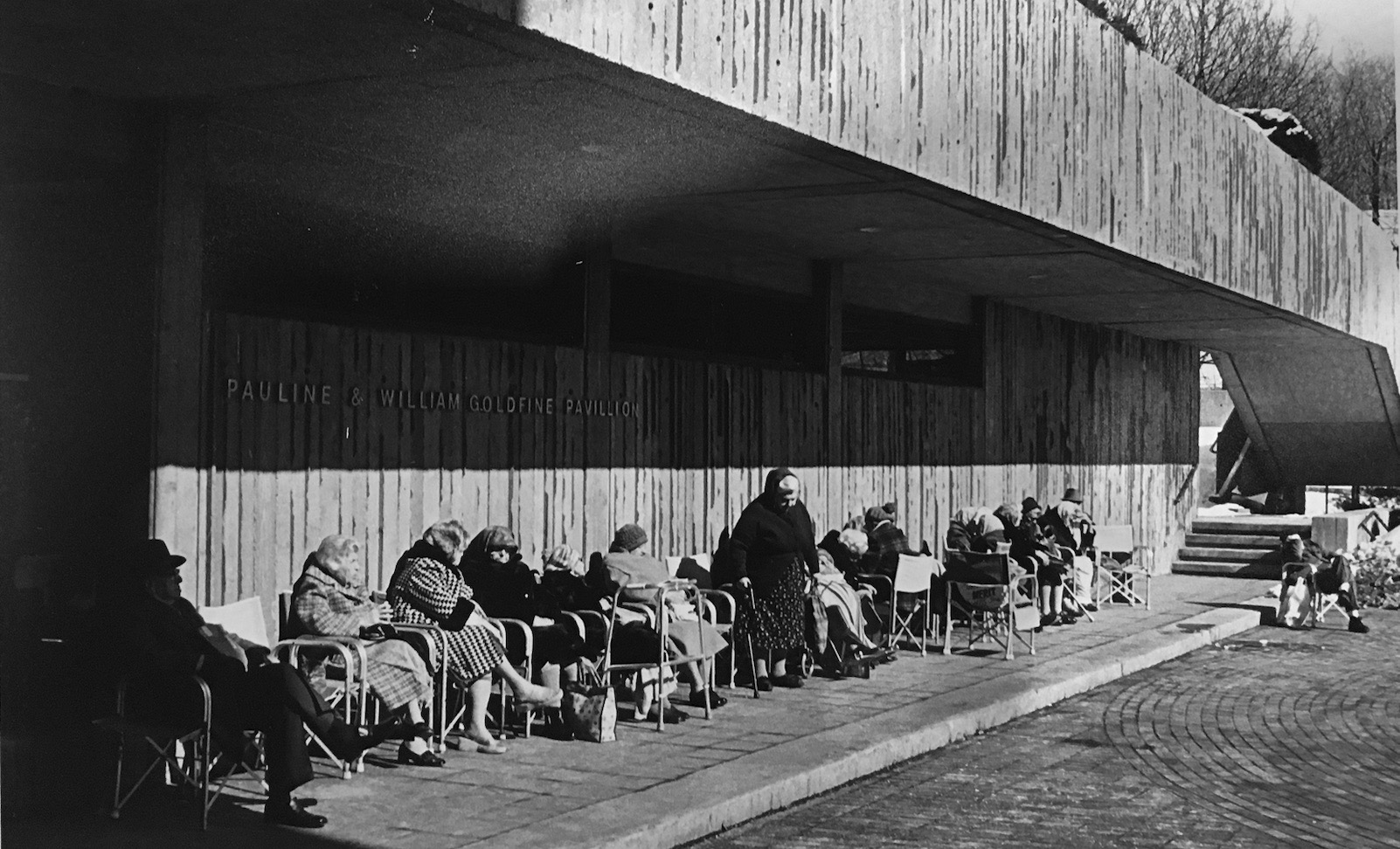 Black and white historic image of elderly residents sitting in front of a nursing home. Representing research from Willa Granger's dissertation.