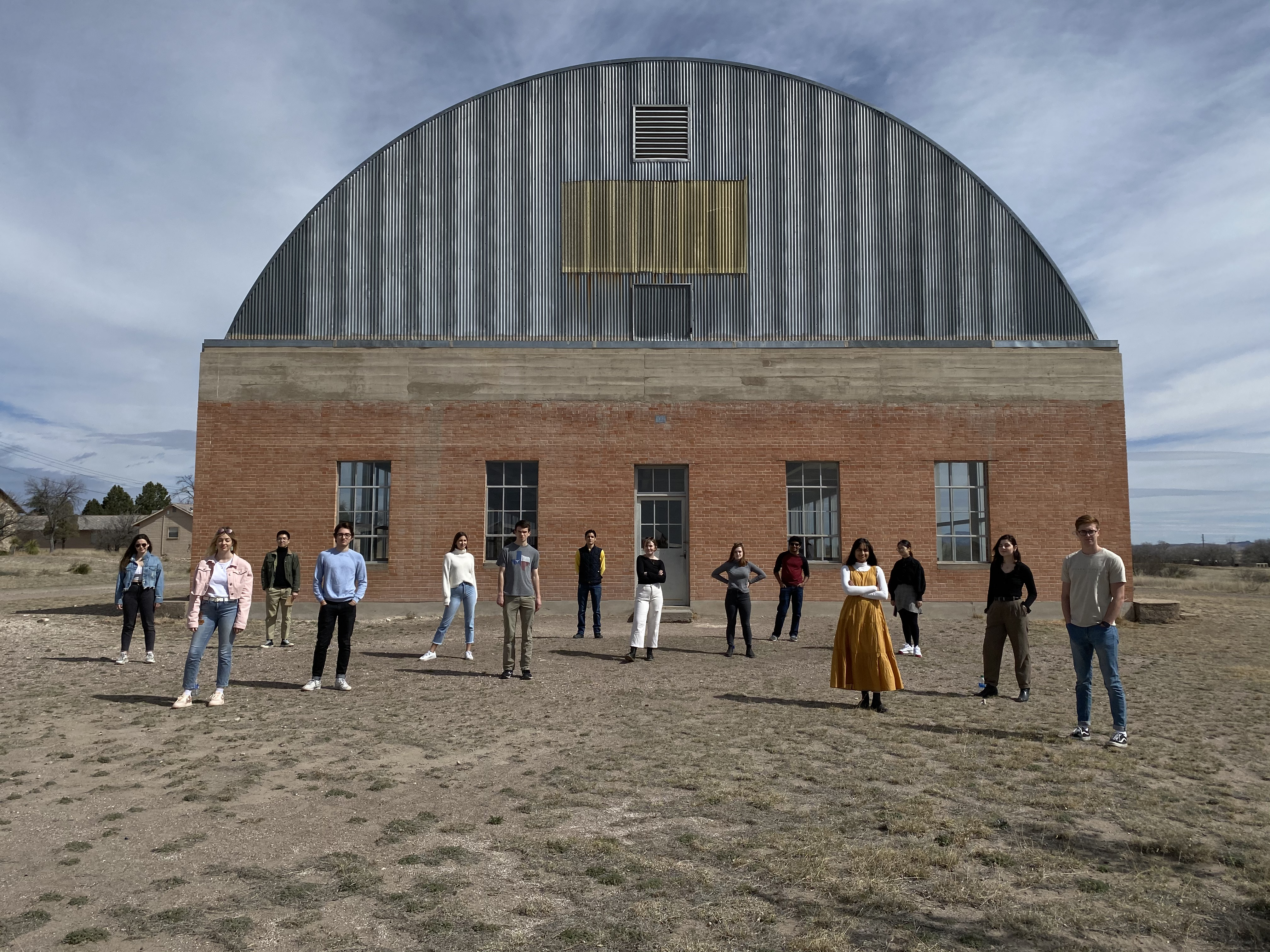 Students standing in front of a round-top building, staggered apart from one another smiling at the camera