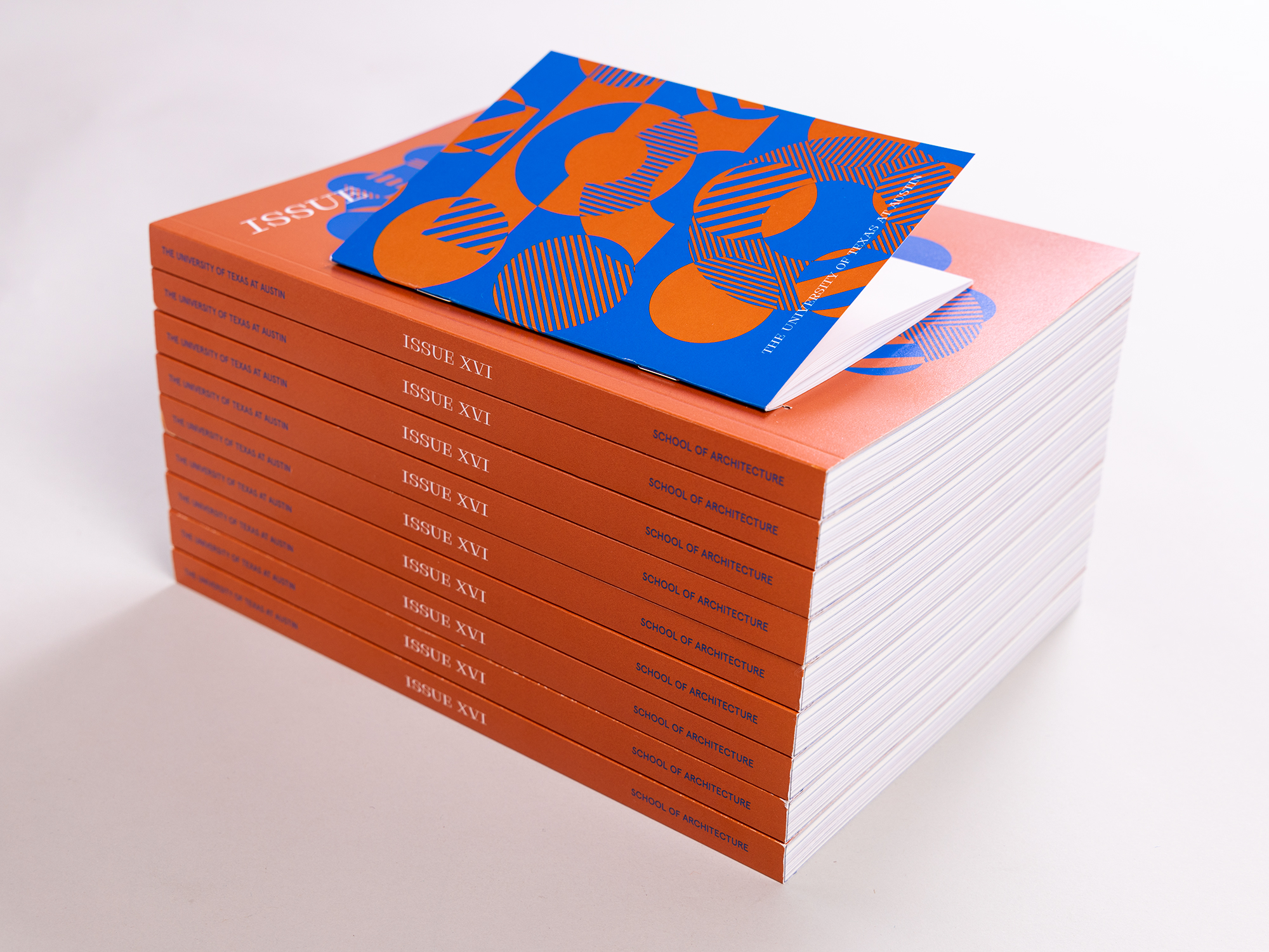 Stack of copies of ISSUE XVI against a white backdrop with the orange spines prominent
