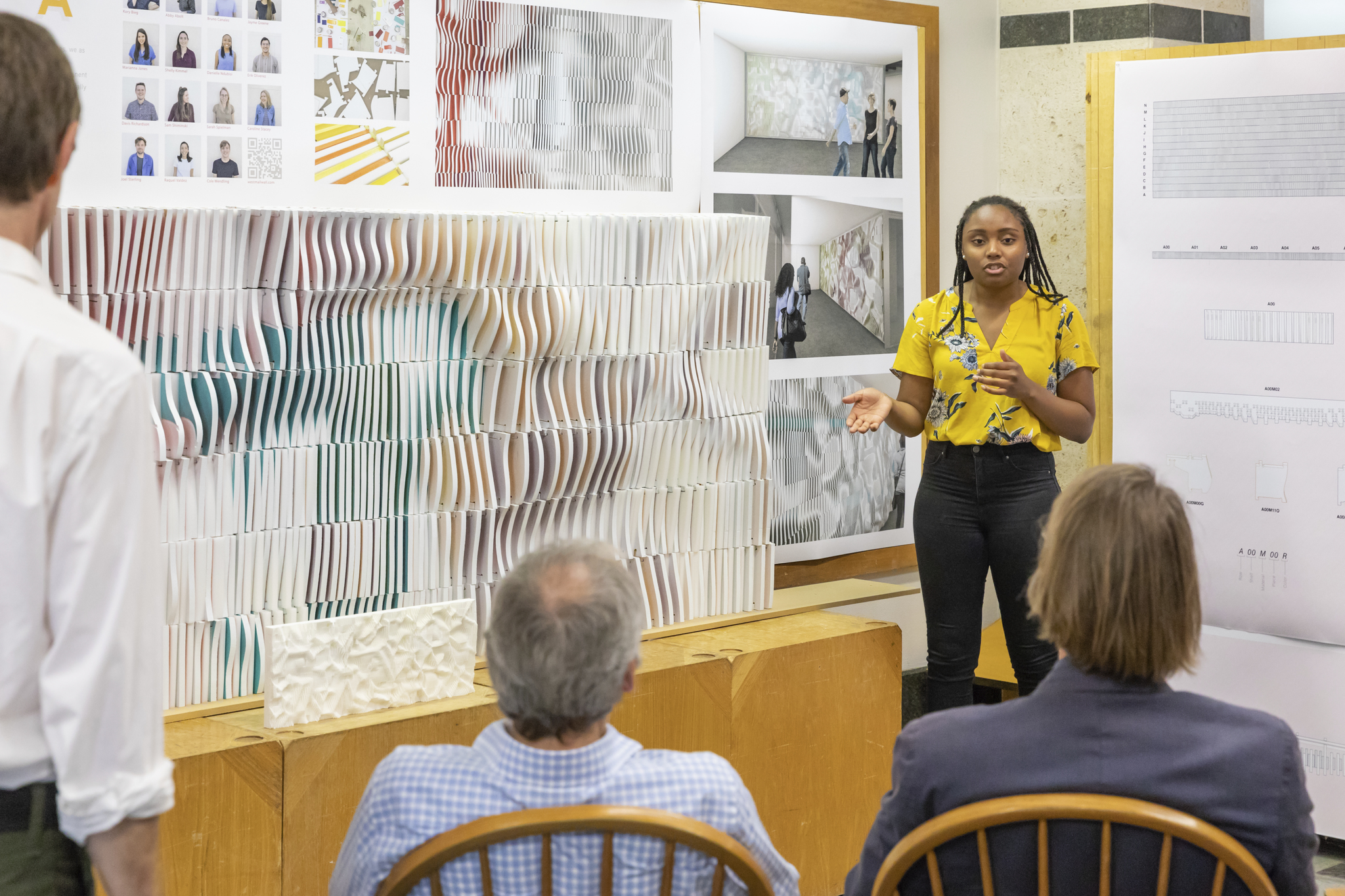 Student gives presentation of ONDA Wall during final reviews to a seated panel