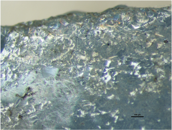 Sample S5, photomicrograph (63x) shows a layered network of fine cracks and iridescence indicating deterioration.