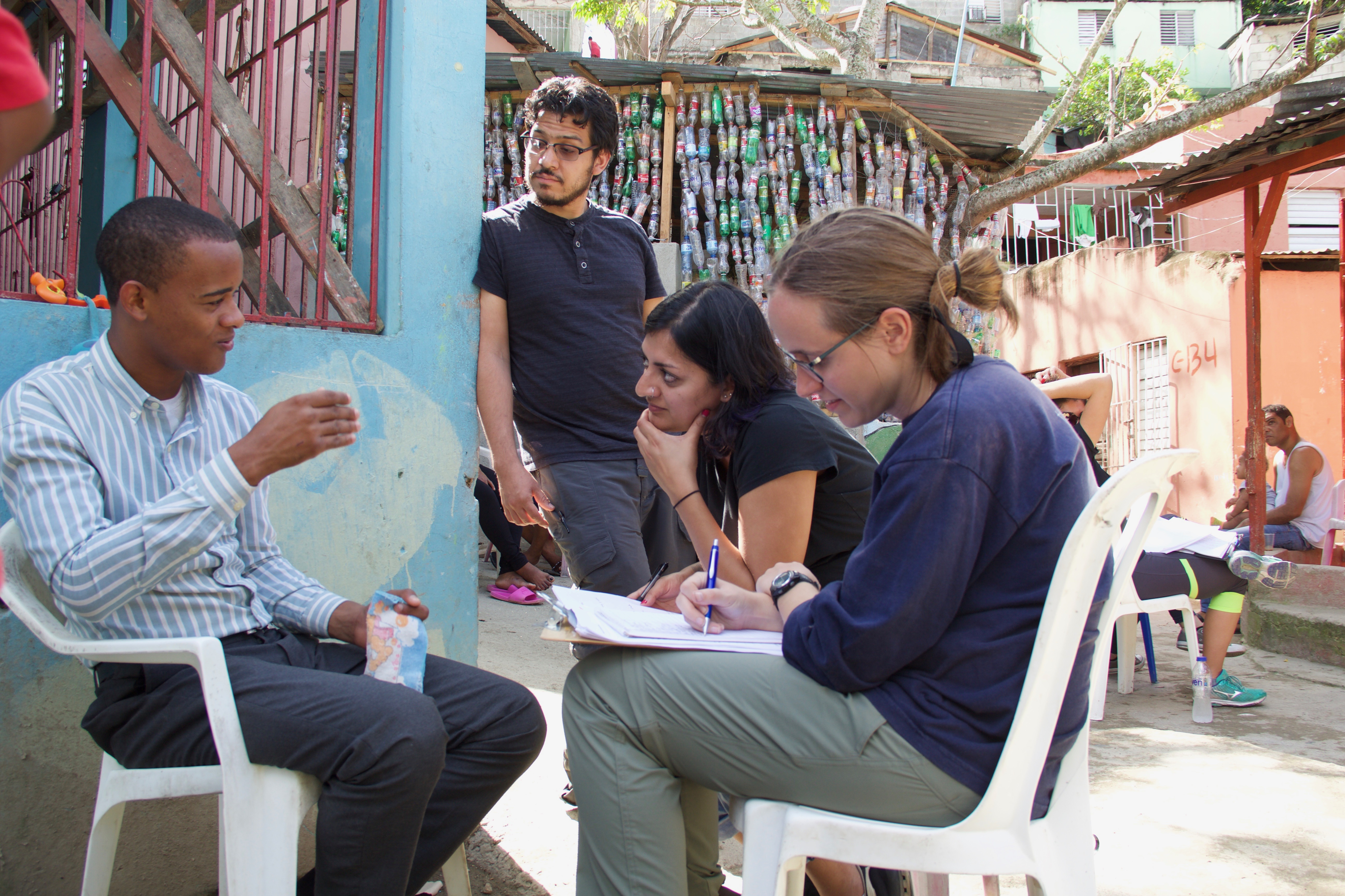 A group of people sit in plastic chairs in front of a colorful, Latin American street. One person is talking and the others are listening intently and taking notes