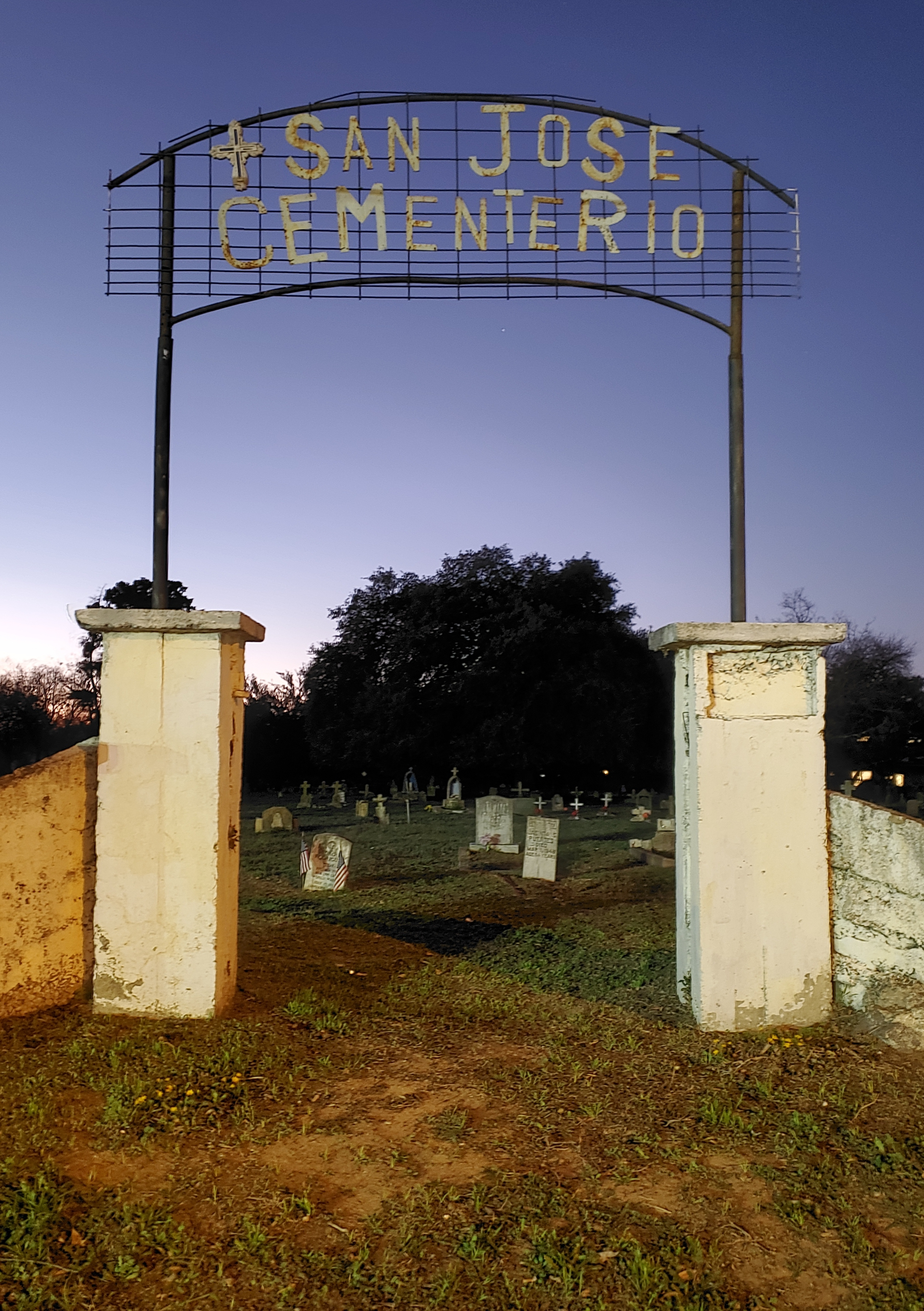 Entrance to the San Jose Cemetery in the Montopolis area of Southeast Austin, looking in through the entryway of the cemetery at dusk, with graves in the background
