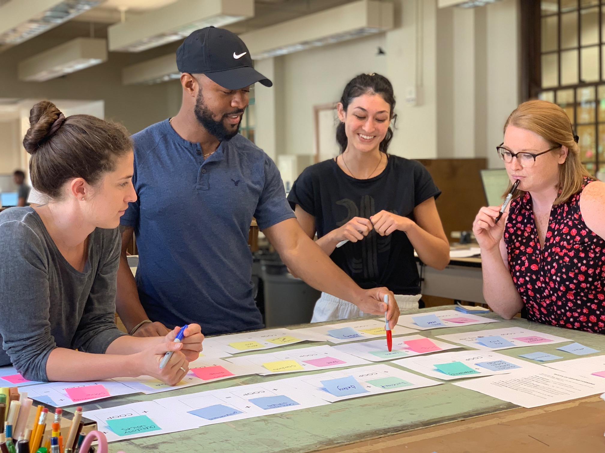 Four students of different genders and races gather around a table to collaborate over post it notes