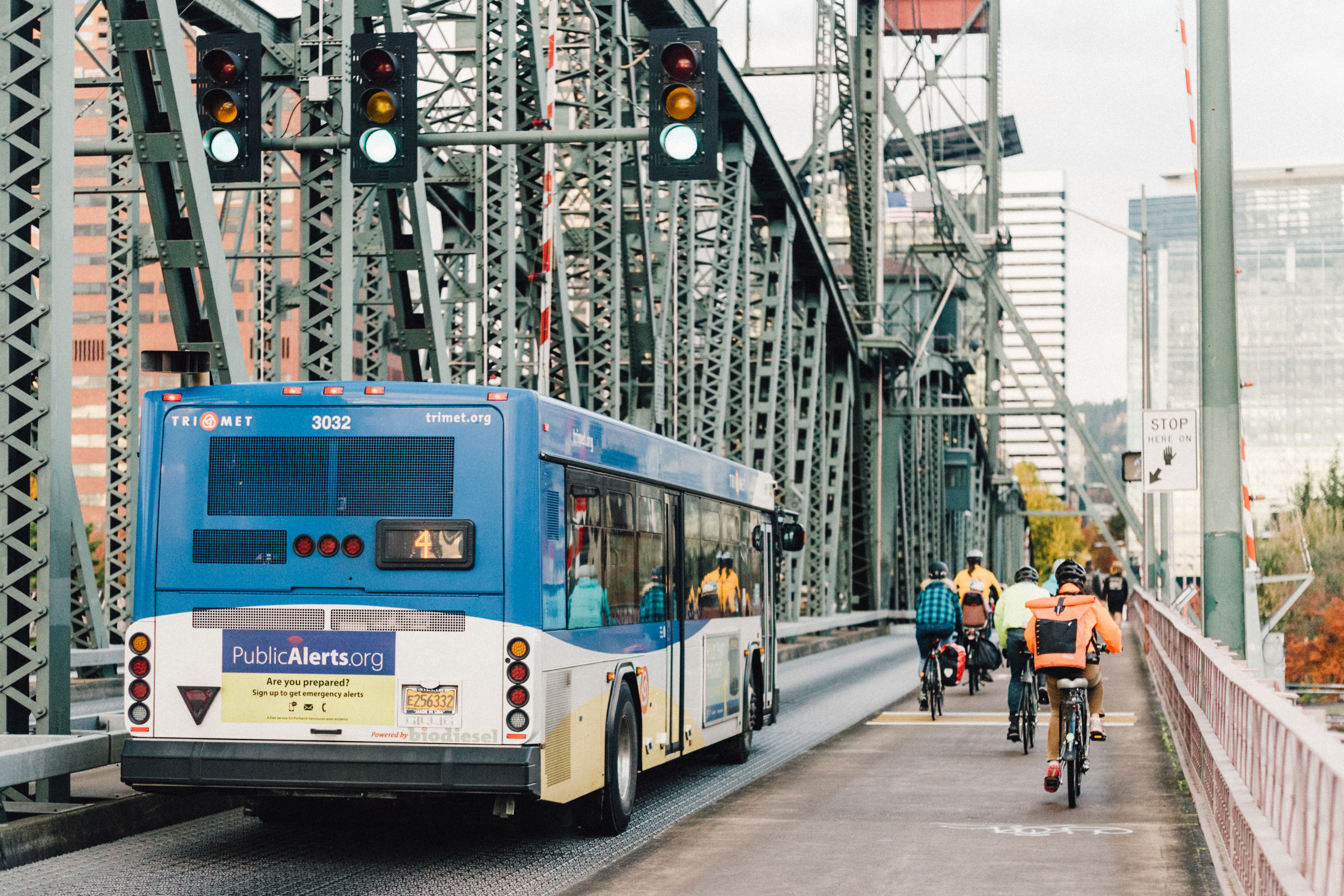 Bicyclists ride alongside a blue bus in downtown Portland