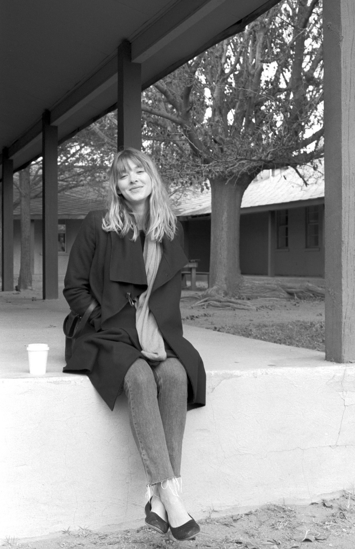 PhD candidate Willa Granger sits on a ledge, smiling at the camera. Shot in black and white.
