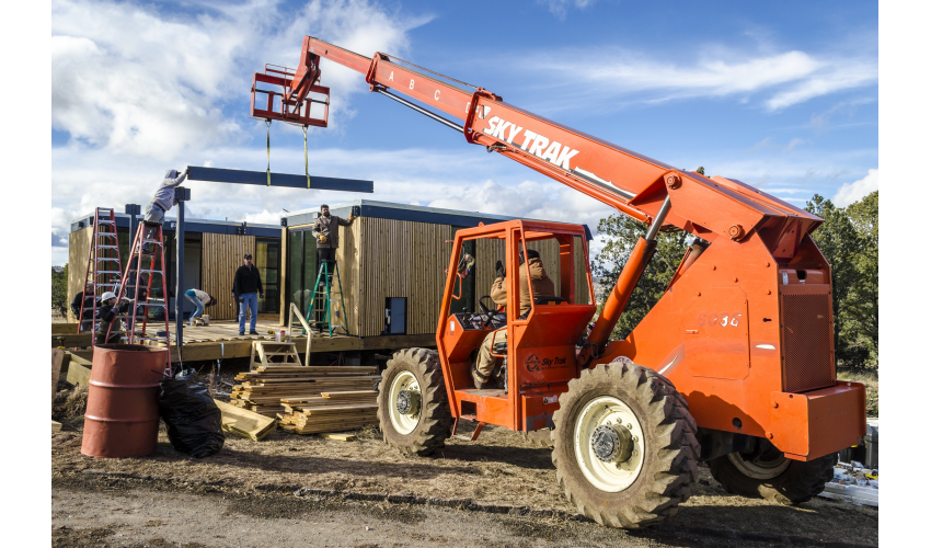An orange crane lifts a steel beam towards a building under construction. A handful of people are gathered outside and on ladders helping to guide the beam in place.
