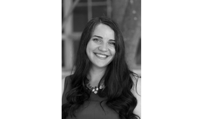Black and white photo of PhD candidate Kathleen Conti smiling at the camera