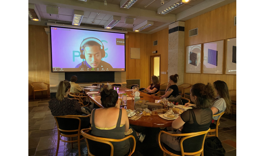 Seven people sit around an oval conference table in front of a projector screen, on which you can see a man in headphones speaking on a Zoom call
