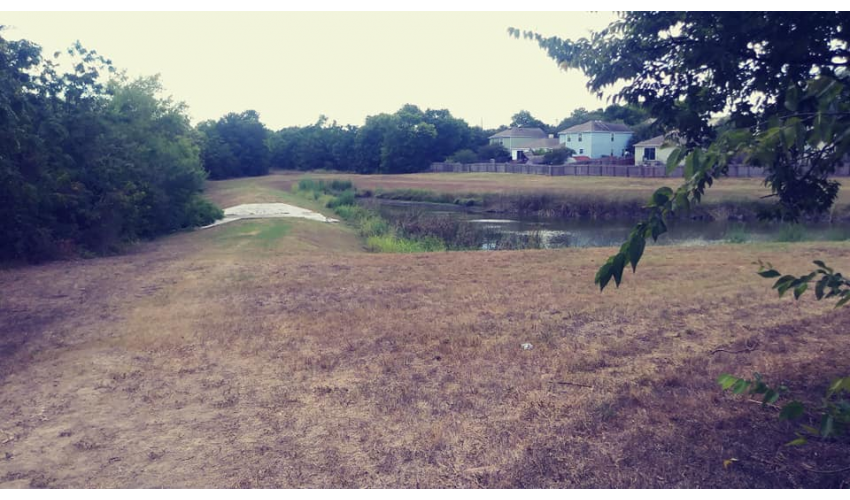 A grassy detention pond in the Dove Springs neighborhood