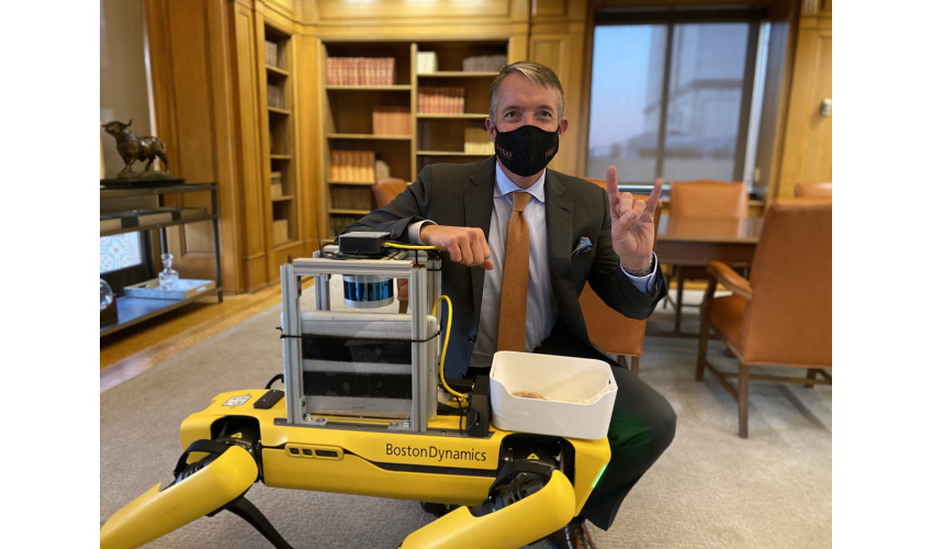 UT Austin President Jay Hartzell poses in his office with a yellow four-legged robot while giving the hook 'em sign