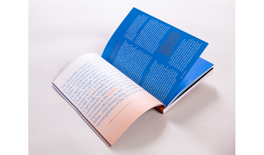 A copy of ISSUE open to the first page. One page is a gradient of orange to white with text on it, the other a bright blue