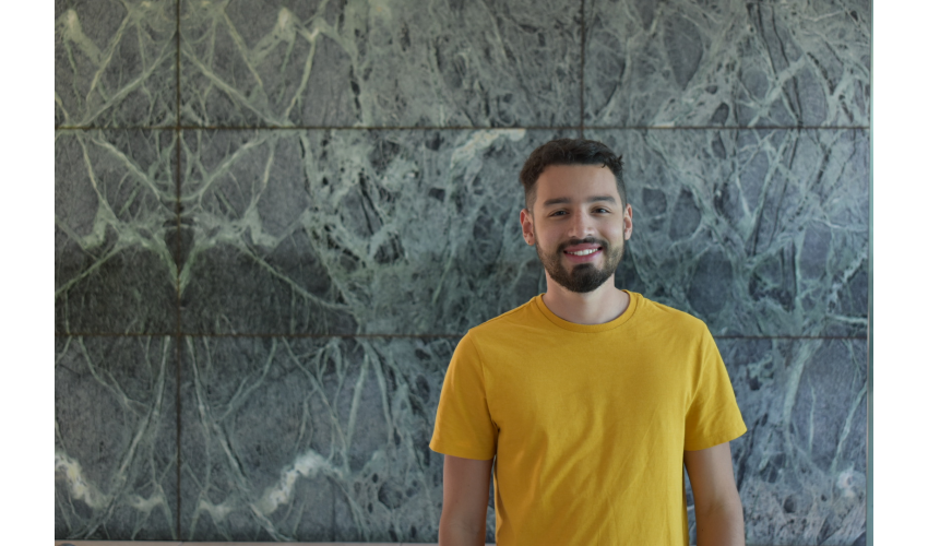 Jorge Zapata in a yellow shirt standing against a textured wall background