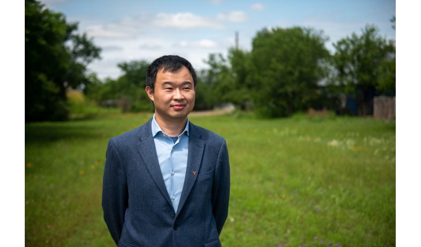 Junfeng Jiao standing in a green field smiling slightly in a suit with a Longhorn pin on his lapel