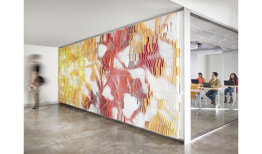 Students sitting in a high-tech classroom behind a digitally manufactured wall comprised of thousands of colorful tiles