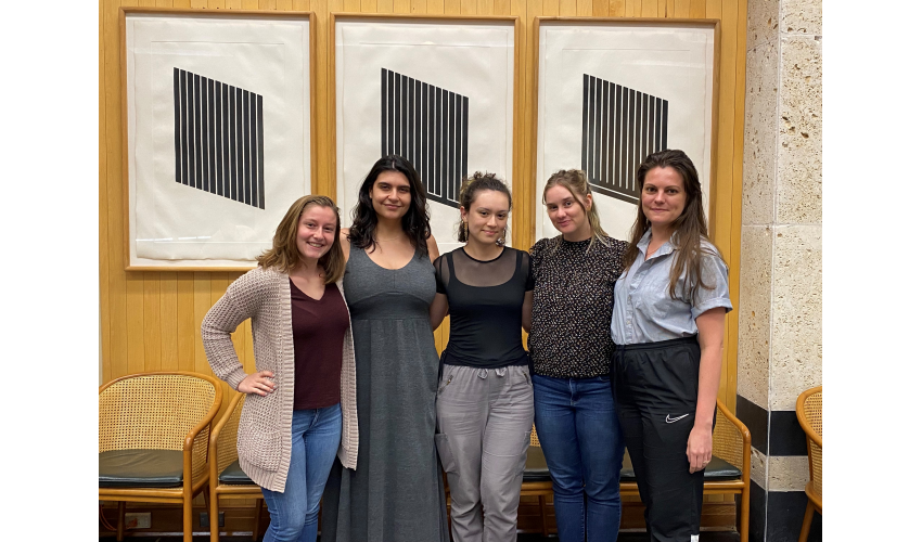 A group of five women stand side-by-side in front of a series of minimalist posters, smiling at the camera as they gather together during the Design Futures Student Leadership Forum