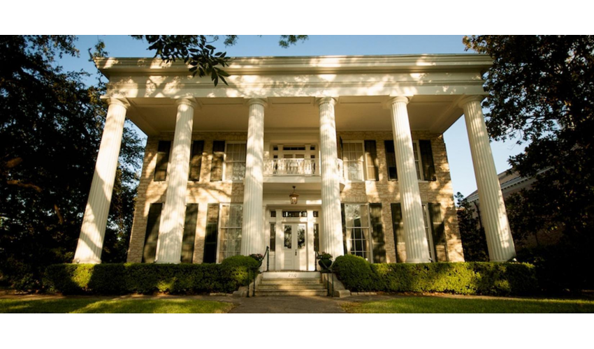 Exterior shot of the Neill Cochran House Museum building, a stately white building with columns, dappled in afternoon light