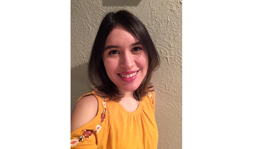 Makayla Ponce in a yellow shirt smiling at the camera in front of a white textured wall