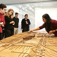 Student leaning over and pointing to a physical model of a city, in front of a handful of reviewers