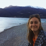 Franny Kyle smiling at the camera with mountains and a lake shoreline in the background