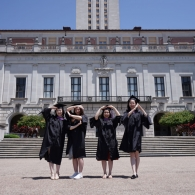 """Four graduates in front of the UT Tower posing in a way that spells """"SOA"""""""
