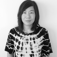 Black and white portrait of Stephanie Choi standing in front of a white wall in a tie dye top