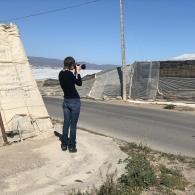 Seen from behind, Aleksandra Jaeschke taking a picture of the exterior of a greenhouse in Almeria, Spain