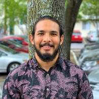 Amir Mirza in a floral shirt smiling at the camera with his back against a tree standing in a parking lot