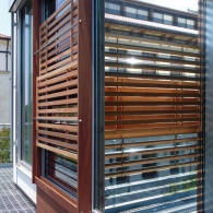 Detail of corner window covered by horizontal wooden slats