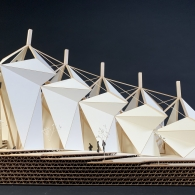 An architecture model of five geometric, white sail-like structures in a row in descending orders of height.