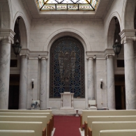 """View of the main chapel with """"Lady of Eternity"""" window by Edgar Miller. View facing west. Window captured in reflected light."""