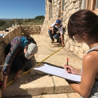 Historic preservation students measure the distance of a stone balcony outside an old structure. One student is seen taking notes on a clipboard, marking the measurements