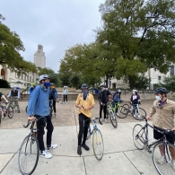 Students on bikes, in helmets and masks, sit at the intersection of the West Mall and Guadalupe Street in front of the UT Tower