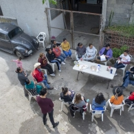 Overhead shot of a group of people sitting in plastic lawn chairs around a table in the streets of Monterrey