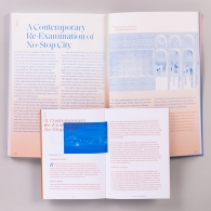 Two page spread of ISSUE XVI with the companion book open to a two page spread slightly on top