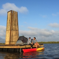 Two students sit on a structure floating in the middle of a body of water. There's a tent on the structure and a kayak on the water below.